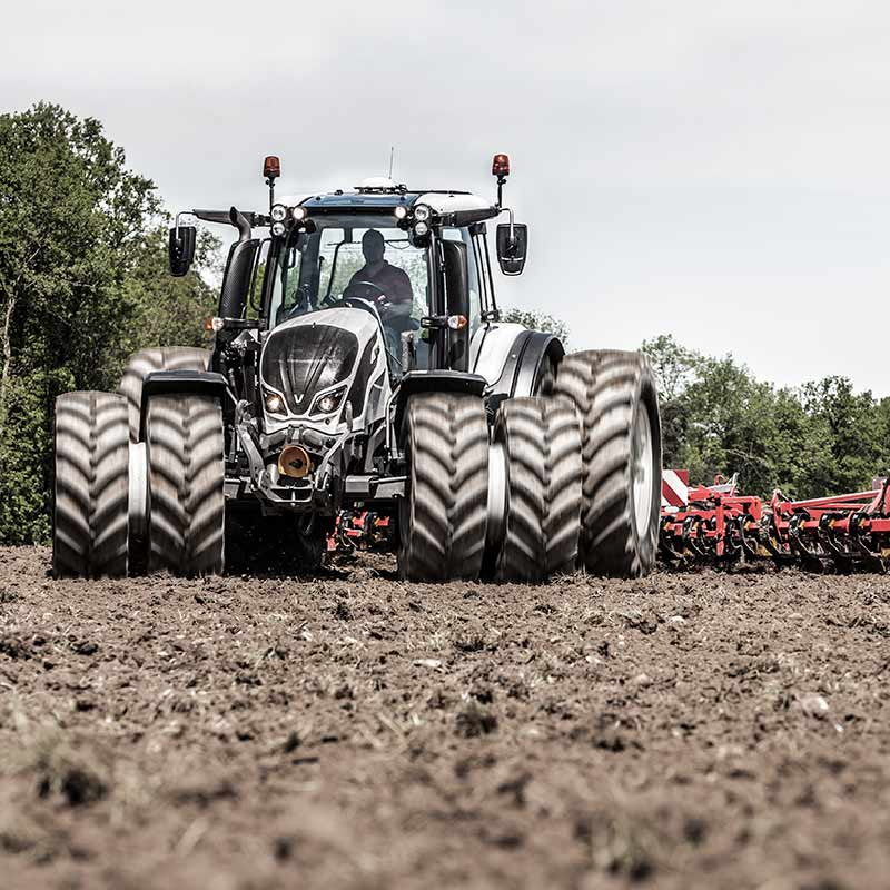 valtra n4 series on a muddy field ploughing with dual wheels